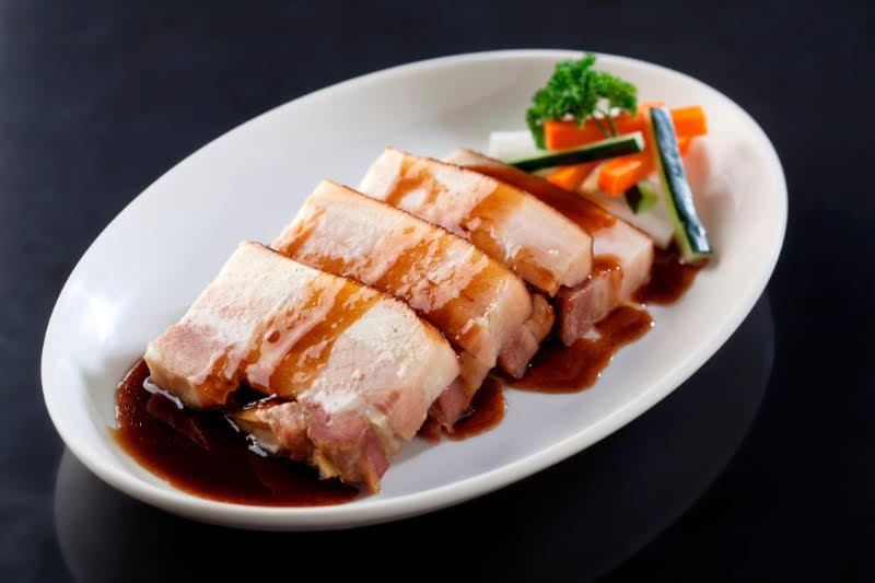 HONEY LECHON: Delicate slices of tender pork belly, roasted for 6 hours on a bed of garlic and lemongrass