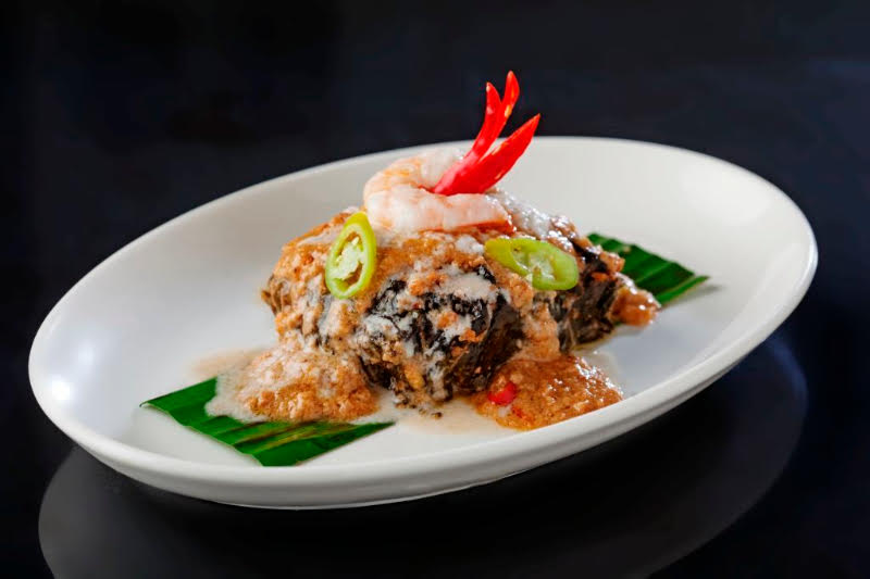 TINUMOK: Coconut noodles and chopped shrimp wrapped in taro leaves stewed in rich coconut cream and flavored with bagoong alamang.
